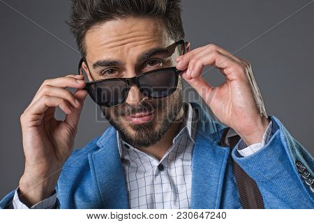 Waist Up Portrait Of Self-confident Successful Businessman Touching-up Shades Glasses. He Is Looking