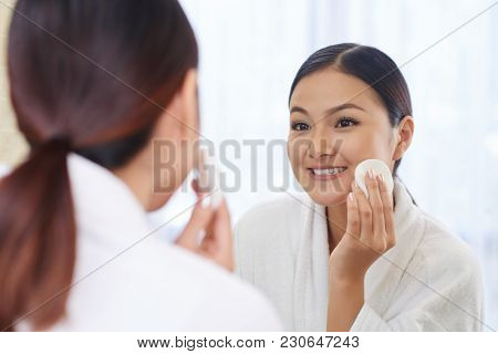 Smiling Pretty Young Woman Removing Make-up With Micellar Water On Cotton Pad