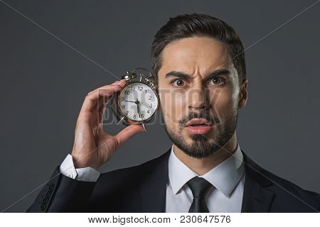 Waist Up Portrait Of Puzzled Man Leaning Ear On Alarm Clock. Isolated On Gray Background