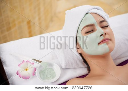 Beautiful Asian Young Woman Lying With Clay Mask On Half On Her Face