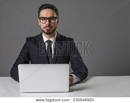 Waist Up Portrait Of Concentrated Young Man Sitting At The White Table With Computer. He Is Looking