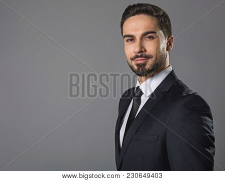 Waist Up Portrait Of Happy Assertive Young Man. Isolated On Gray Background. Copy Space In Left Side