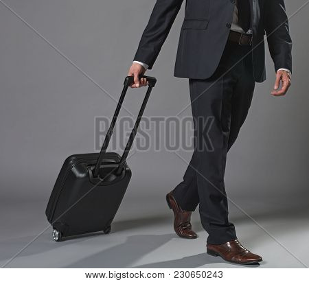 Travelling Businessman In Black Suit With Rolling Backpack. Close Up Of Legs