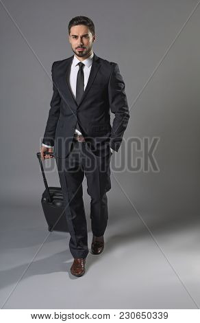 Full Length Portrait Of Young Assured Man Going On Business Trip With Luggage. He Walking And Keepin