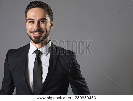 Sense Of Joy. Waist Up Portrait Of Bearded Joyful Man In Business Suit, He Is Looking At Camera With