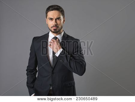 Waist Up Portrait Of Young Strong Handsome Man With Look Of Indignation. Isolated On Grey Background