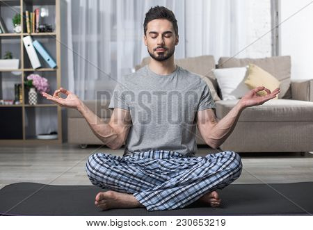 Portrait Of Calm Bearded Male Sitting On Yoga Carpet In Living Room