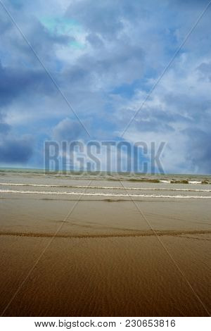 Sand, Water And Blue Sky Make Up This Background.