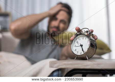 Focus On Alarm Clock Standing On Table. Man On Background Is Turning It Off