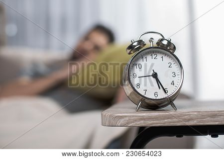 Focus On Alarm Clock Standing On Table. Man Is Dreaming On Background