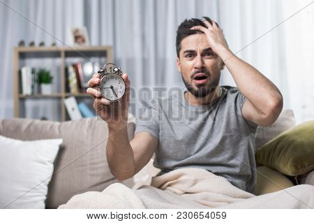 Waist Up Portrait Of Shocked Handsome Man Sitting On Couch. Focus On Clock He Is Showing To Camera I