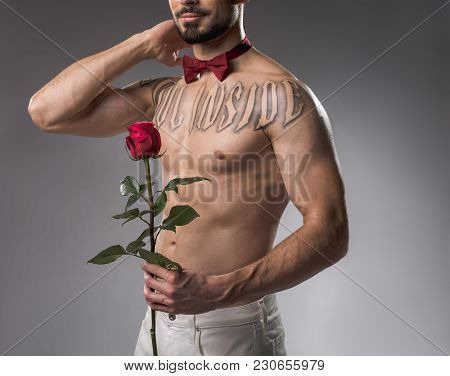 Serene Bodybuilder Posing Without Cloth On His Upper Body. He Is Holding Rose In Hand. Isolated On B