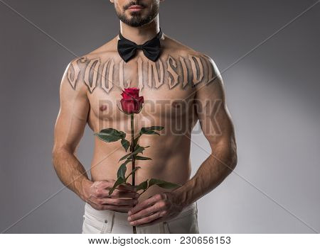 Calm Strong Guy Posing Without Shirt And With Rose In Hands. Isolated On Background