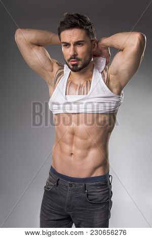 Portrait Of Solemn Sexy Macho With Muscular Body Disrobing His Torso. Isolated On Background