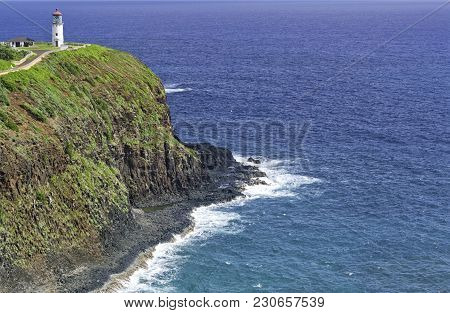 An Old White Lighthouse With A Red Roof On A Remote Cliff Over A Calm Ocean In The Hawaii Islands In