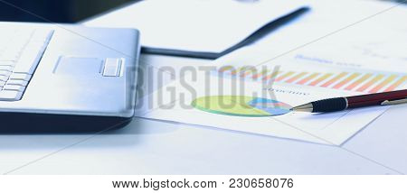 Workplace With Laptop And Working Documents For The Business Team In A Modern Office. The Photo Is A