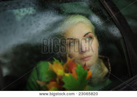 Portrait of beautiful Woman in Auto durch nasses Glas blicken. Closeup.