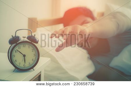 Adult Male On Bed Is Reaching To Stop Alarm Clock