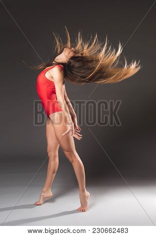 Side View Of Well Built Longhaired Girl In Red Tricot Doing Active Exercise