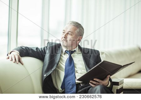 Successful Businessman With Business Documents Sitting On A Sofa In A Private Office