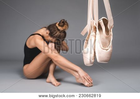 Focus On Pointe. Exhausted Ballet Dancer Taking Rest On Background