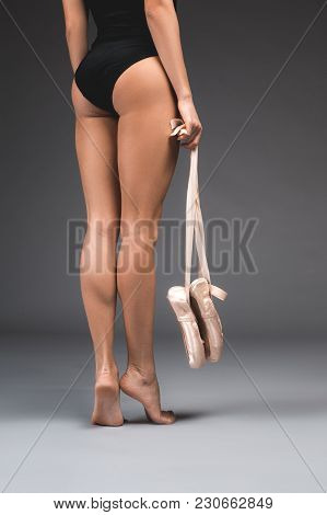 Sportive Girl Demonstrating Slim Feet While Standing With Her Back And Holding Pointe In Hands. Clos