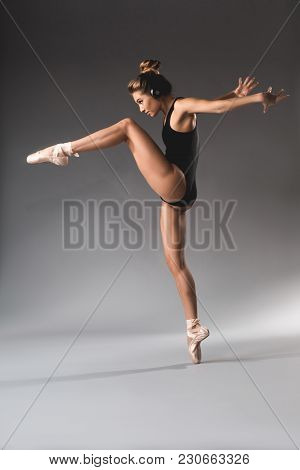 Side View Profile Of Confident Sportive Girl With Headphones Balancing On One Leg
