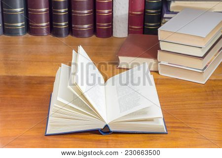 Open Book With Blue Hardback On A Wooden Table At Shallow Depth Of Field With Blurred Text Against O