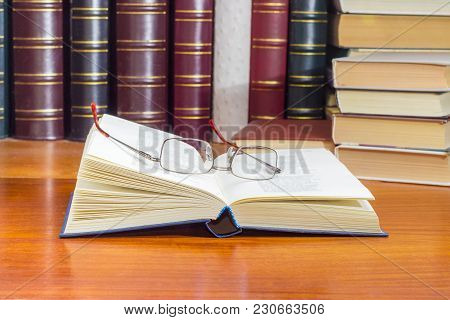 Open Book In Blue Hardcover And Classic Mens Eyeglasses On It On A Wooden Table At Selective Focus W