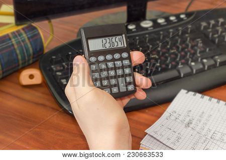 Modern Electronic Pocket Calculator With A Liquid-crystal Display In The Hand Of Schoolboy Over The