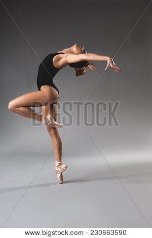 Side View Of Lady With Plastic Figure Bending Backwards. She Is Wearing Black Gymnastic Clothes