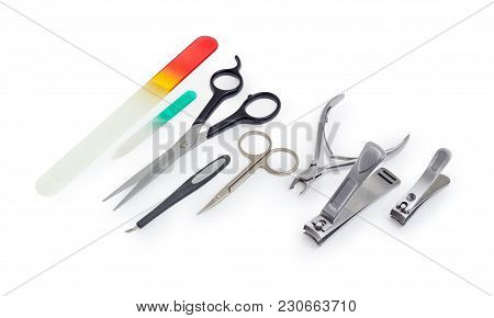Different Scissors, Nail Clippers, Nail Files And Other Hand Tools For Nail Care On A White Backgrou