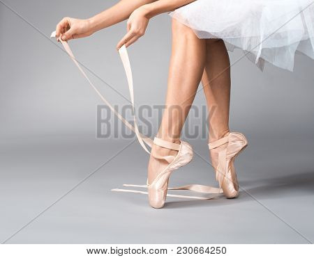 Close Up Of Ballerina Hands Pulling On Ribbons On Her Dancing Shoes