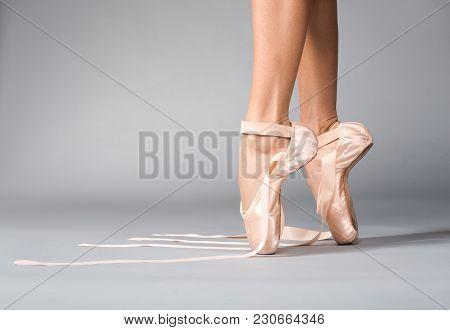 Close Up Of Ballerina Legs In Satin Footwear Standing On Tiptoe. Untied Ribbons Lying On The Floor.