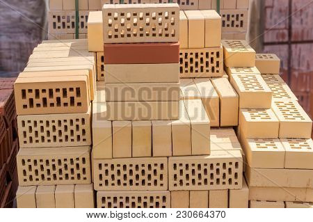 Yellow Perforated Bricks With Rectangular Holes On Pallet Among Of Other Bricks On An Outdoor Wareho