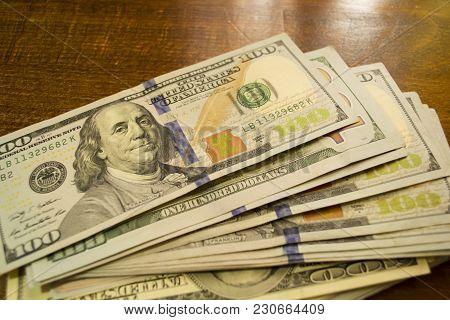 Money On  Wooden Background. Stack Of One Hundred Dollars Bills On Wooden Desk