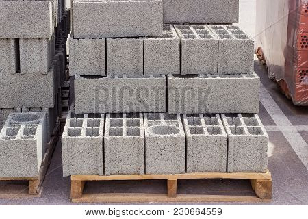 Perforated Concrete Masonry Units On A Wooden Pallets Among Other Building Materials On An Outdoor W