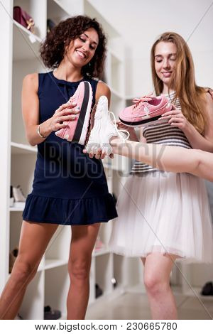 Young Pretty Lady Standing At One Leg While Her Friend Checking New Footwear Size Comparing It With