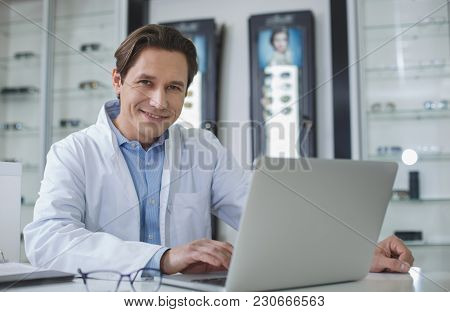 Portrait Of Beaming Male Ophthalmologist Working With Laptop While Looking At Camera. Optician Store