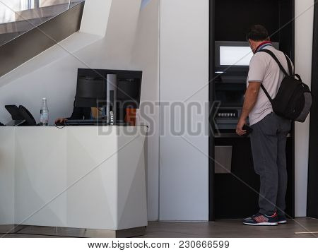 Milano, Italy - September 2015: Cash Machine, Atm And Professional Woman At Front Office Desk.