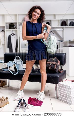 Beautiful Female Shopper Standing Looking Back At Camera In New Short Dress Holding Backpack Wearing