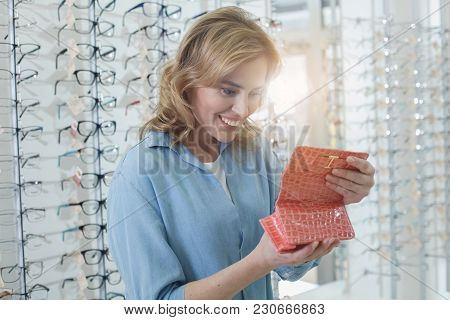 Portrait Of Cheerful Woman Looking At Spectacle Case. Different Spectacles Locating On Shelves. Eye