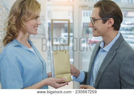 Side View Smiling Female Giving Package To Beaming Man. They Standing In Optician Shop. Ophthalmolog