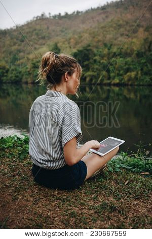 Woman alone in nature using a digital tablet with entertainment application on the screen internet connection and leisure concept
