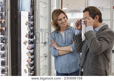 Happy Woman With Crossing Arms Talking With Man. He Wearing Spectacles And Looking At Mirror. Visito
