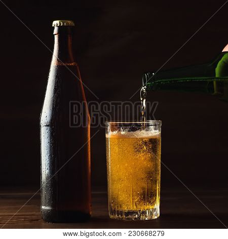 Pouring Foaming Beer Into Glass Mug With Drops Near Cold Beer Bootle On Wooden Table, Craft Brewing
