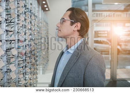 Side View Pensive Man Looking At Different Spectacles While Standing In Optician Shop. Eyesight Corr
