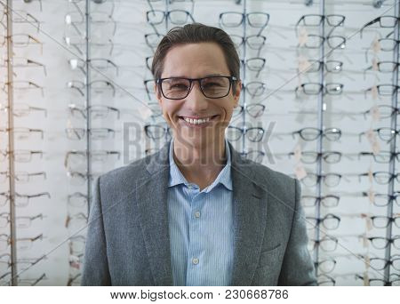 Portrait Of Beaming Man In Spectacles Looking At Camera While Standing In Optician Shop. Visitor Buy