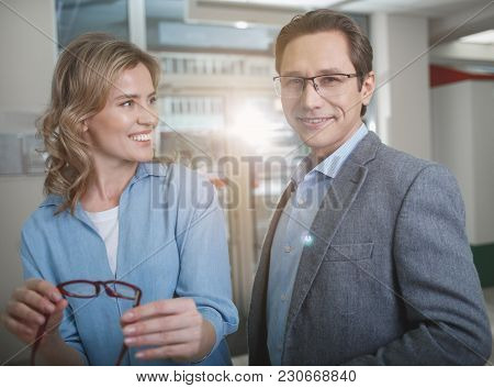 Portrait Of Happy Woman And Outgoing Male Situating In Optician Store. Female Holding Eyeglasses In