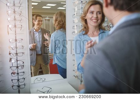 Portrait Of Outgoing Male Wearing Eyeglasses While Telling With Female. He Standing Opposite Mirror.